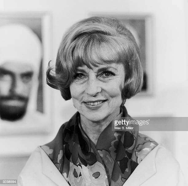 Headshot of American actor Agnes Moorehead smiling at the premiere of director Basil Deardon's film 'Khartoum' Behind her is a promotional portrait...