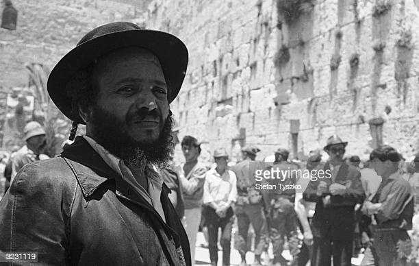 A bearded Jewish man looking pensive at the Western or Wailing Wall in the old city of Jerusalem as soldiers mix with worshippers during the Six Day...