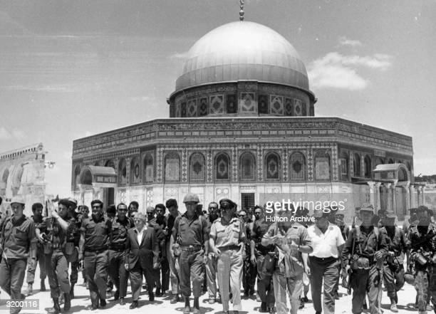 Israeli statesmen David BenGurion and Yitzhak Rabin lead a group of soldiers past the 'Dome of the Rock' on the Temple Mount on a victory tour...