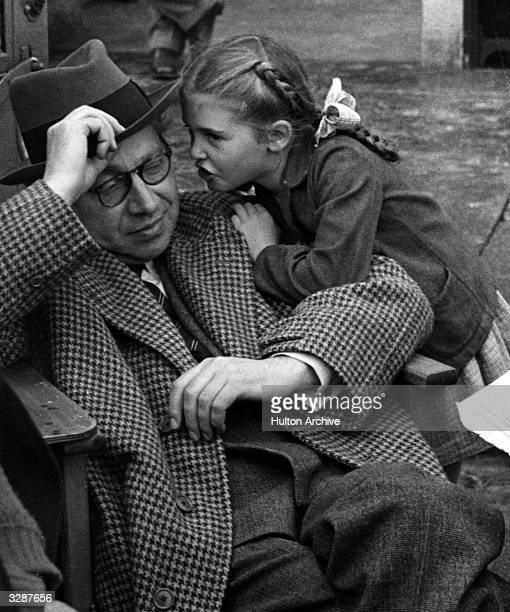 Alexander Korda the former Hungarian film producer who worked with MetroGoldwynMayer slouched in a chair with a little girl with pigtails leaning on...