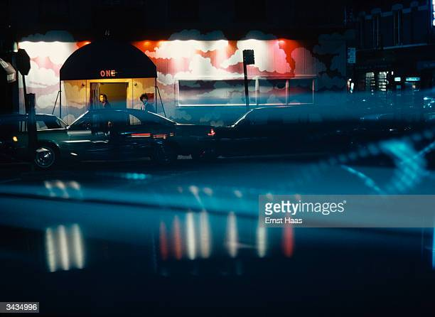 Cars outside an entrance way seen through a windscreen at nightime