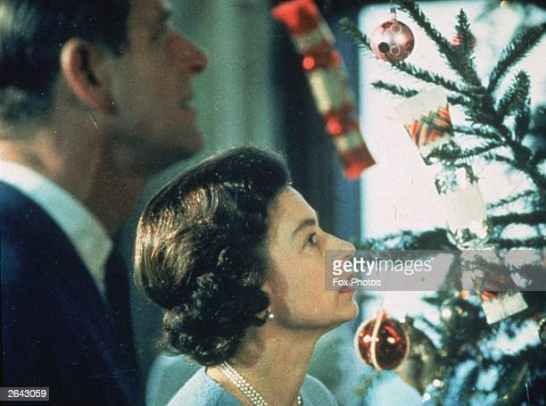 Queen Elizabeth II and Prince Philip look at their decorated Christmas tree during the filming of a television special about life in the British...