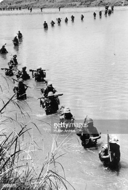 US Marines of the 1st Division cross the Vu Gia River holding their weapons across their shoulders in pursuit of a Viet Cong force Vietnam