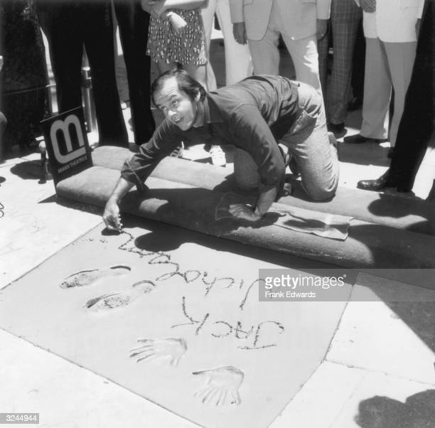 American actor Jack Nicholson kneels down and signs his name in wet cement next to his hand and foot imprints outside Grauman's Chinese Theater,...