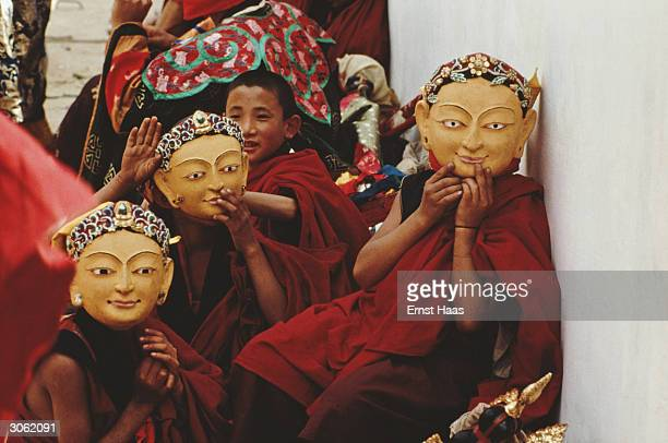 Boy monks try on masks in preparation for a mystery play to be performed for royal guests during the coronation ceremony of King Jigme Singye...