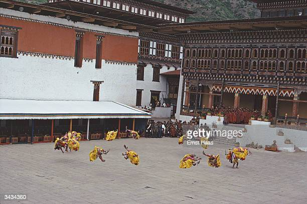 In the courtyard of Tashichodzong Castle residence of the chief Lama and seat of the Royal Government of Bhutan specially trained lay dancers leap...