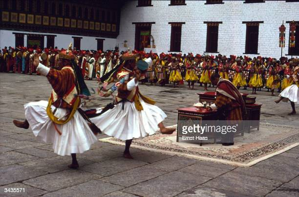 The great courtyard at Tashichodzong Castle Thimphu where food is being laid out on an ornate table and ceremonial dances are being performed in...