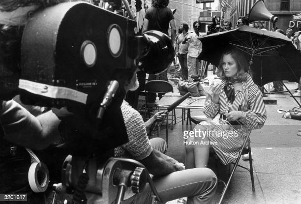 American actor Cybill Shepherd sits on the sidewalk with an umbrella and a cup being interviewed during the shooting of director Martin Scorsese's...