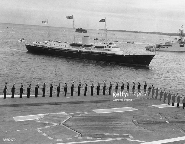 The crew of the aircraft carrier HMS Ark Royal line the deck to salute the Queen Elizabeth as she passes by on board the Royal Yacht Britannia during...