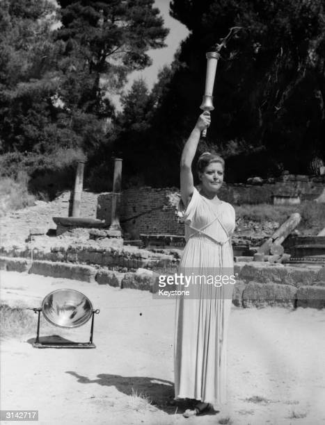 An actress wearing an ancient Greek tunic carries the olympic torch after it was lit by sun rays at Olympia Greece It is then carried to Moscow the...