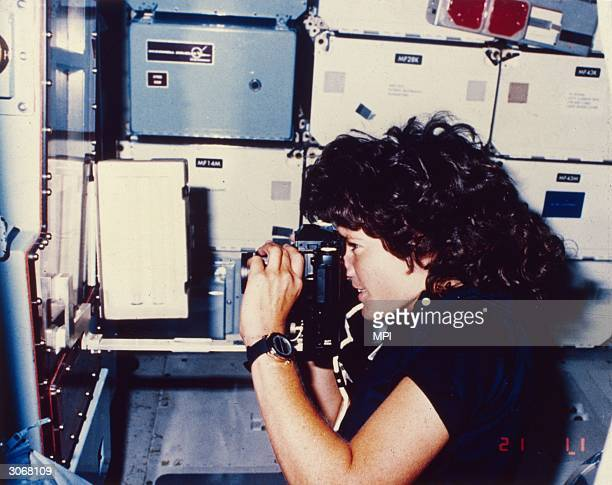 Astronaut Sally Kirsten Ride the first American woman in space takes a photograph during her earth orbit in the Challenger shuttle STS7