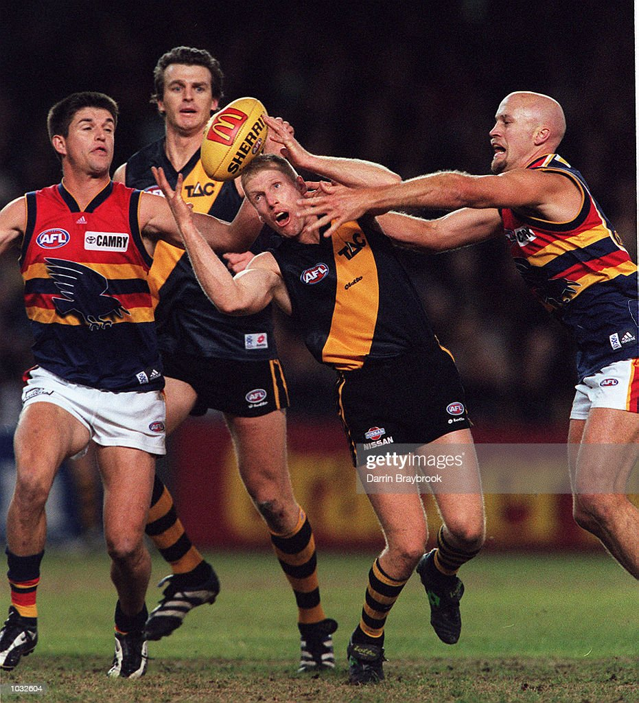 Matthew Knights #33 for Richmond, attempts to keep the ball away from Nathan Basset #8 and Nigel Smart #7 for Adelaide, during the round 13 match between the Adelaide Crows and Richmond Tigers which was played at Colonial Stadium, Melbourne, Australia Mandatory Credit: Darrin Braybrook/ALLSPORT