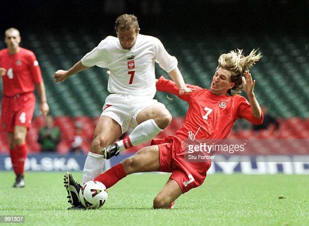 Marek Kozminski of Poland gets past Robbie Savage of Wales during the match between Wales and Poland in the 2002 World Cup Qualifying Group 5 at...