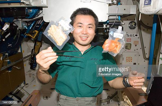 3 June 2009 Japan Aerospace Exploration Agency Astronaut Koichi Wakata Expedition 20 Flight Engineer Holds Chopsticks Near Two Food Containers...