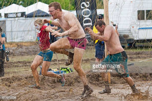 Competitors fight through electric shock wires in one of twenty obstacles in the Tough Mudder adventure endurance race at Michigan International...