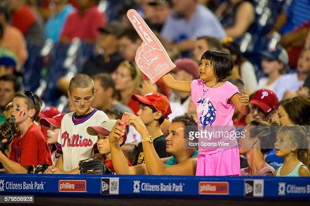 A young fan waves her pink foam finger to support her team during the MLB game between the Milwaukee Brewers and the Philadelphia Phillies played at...