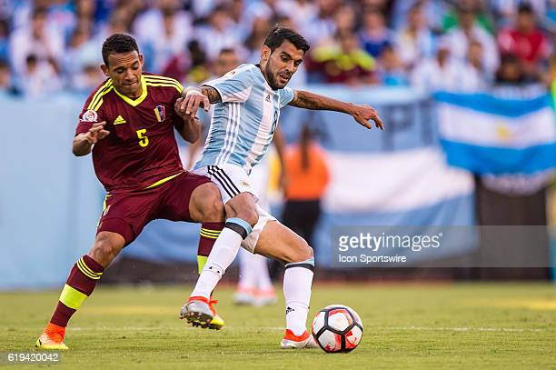 Argentina midfielder Augusto Fernandez shields the ball from Venezuela midfielder Arquimedes Figuera in the 1st half during the Copa America...
