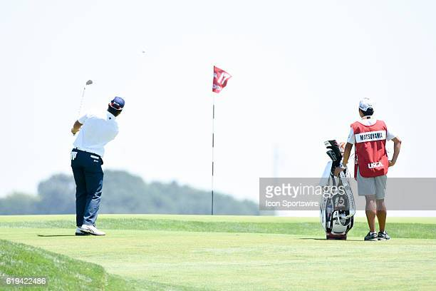 Hideki Matsuyama hits his approach to the 17th green as caddie Daisuke Shindo looks on during a rain delayed first round of the US Open at Oakmont...