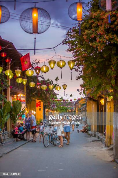 june 2017 hoi an, vietnam - tourists walk down the colonial streets in historic old town hoi an. lanterns illuminate the walkways. - hoi an stock pictures, royalty-free photos & images