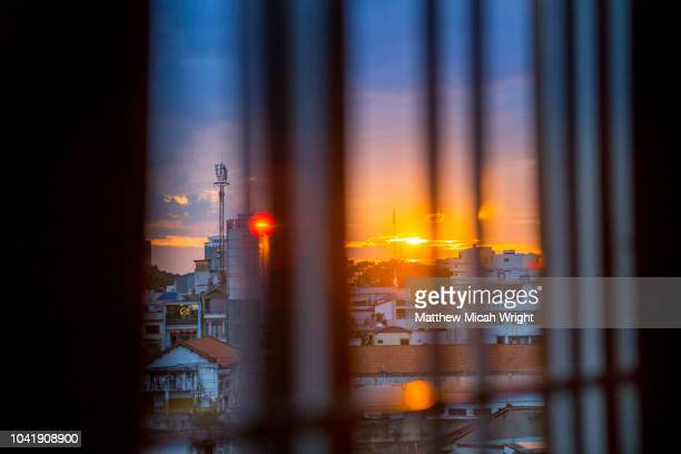 June 2017 Saigon, Vietnam - Sunset descends over the rooftops of Ho Chi Minh City as seen from a local window.