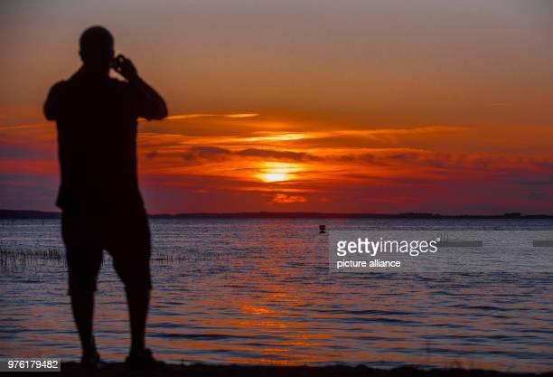 June 2018, Boek, Germany: A man watching the sun set at the Muertiz. Photo: Jens Büttner/dpa-Zentralbild/dpa