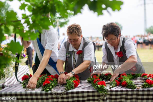 Members of the shooting club prepare in advance of the proclamation of the marksmen of the shooting fair in Garßen near Celle the king chains and the...