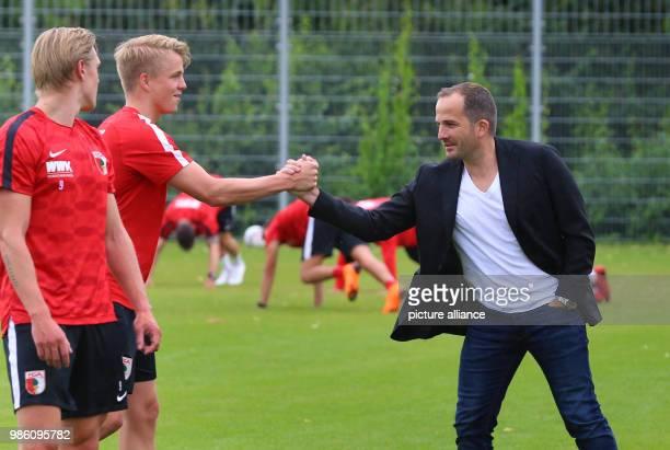 Augsburg's trainer Manuel Baum greets Felix Götze Photo KarlJosef Hildenbrand/dpa