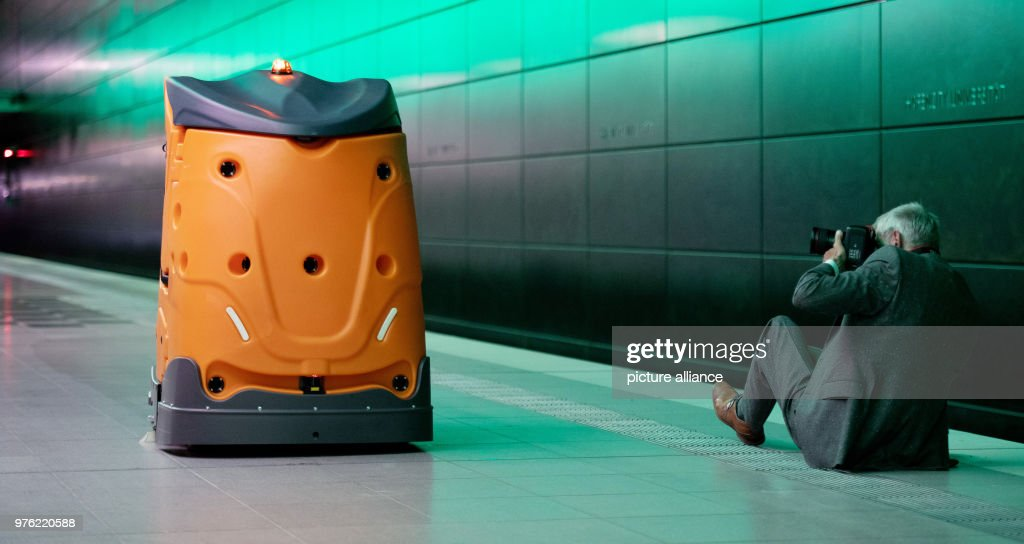 A man takes a picture of the autonomous cleaning robot called 'Taski