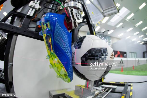 The 'Telstar 18' the official ball of this year's FIFA World Cup in Russia sits in front of the shoe of a kicking robot at the research lab 'Future...