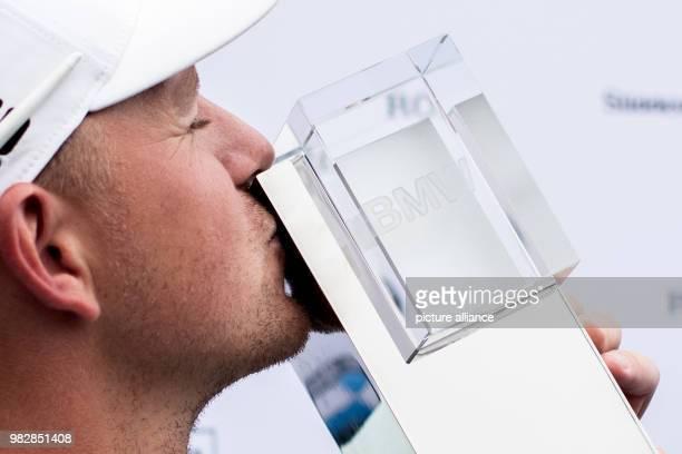 Golf European Tour International Open mens singles 4th round The winner Matt Wallace a golfer from England kissing the trophy Photo Marcel Kusch/dpa