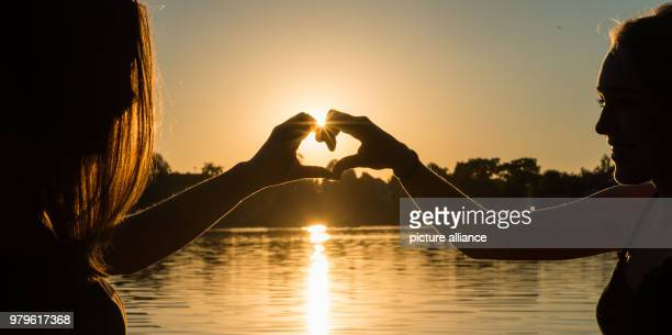 June 2018, Germany, Weissling: Lynn and Annika enjoy a lakeside picknick and form a heart with their hands as the sun sets. Photo: Lino Mirgeler/dpa