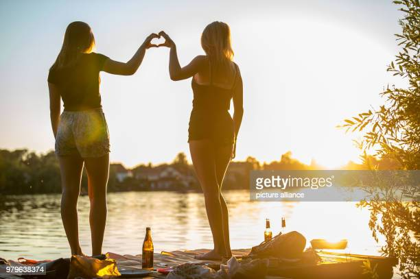 Lynn and Annika enjoy a lakeside picknick and form a heart with their hands as the sun sets Photo Lino Mirgeler/dpa