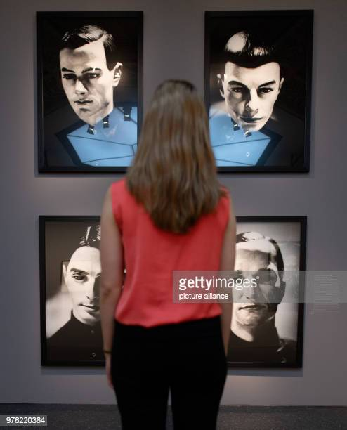 A woman stands in the exhibition 'Anton Corbijn The Living and the Dead' at the Bucerius Kunst Forum in front of the portraits of the band Kraftwerk...