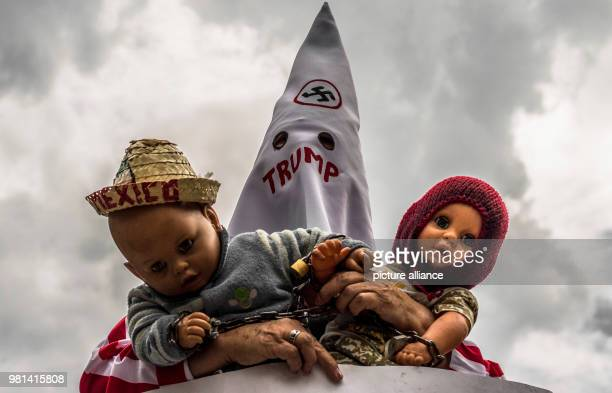 A man dressed up a a KiKluxKlan member holds two puppets during a protest against the migration policies of USA The protest takes place in front of...