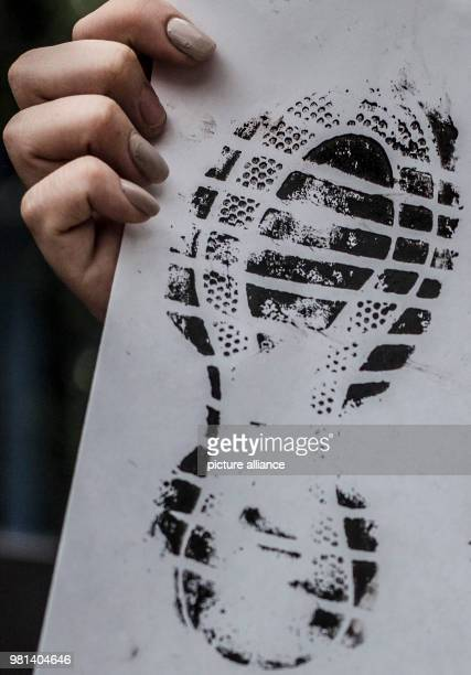 A protester holds up a banner with an image of a shoe sole representing the migrants during a protest against the migration policies of USA The...