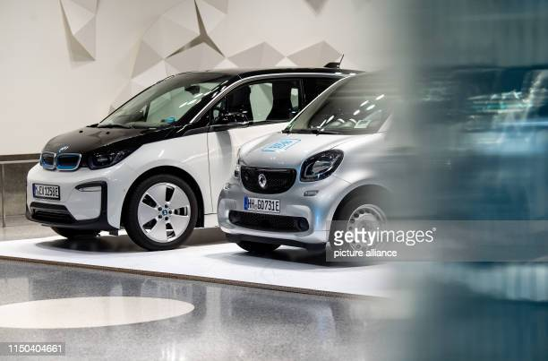 June 2019, Baden-Wuerttemberg, Stuttgart: A BMW i3 from DriveNow and a Smart Fortwo from Car2Go are on display in a current exhibition at the...