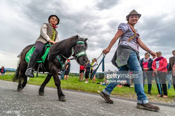 A boy rides a small horse at the Kötztinger Whitsun Ride The procession with around 900 riders is one of the oldest Bavarian customs events The men's...