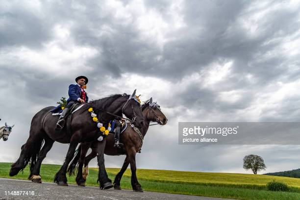 Participants of the Kötztinger Whitsun Ride ride with their horses on a street The procession with around 900 riders is one of the oldest Bavarian...
