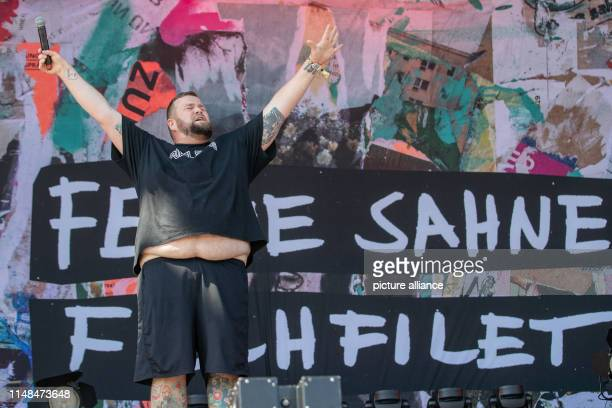 Jan Monchi Gorkow singer of the German punk band Feine Sahne Fischfilet stands on stage at the openair festival Rock im Park and stretches both arms...