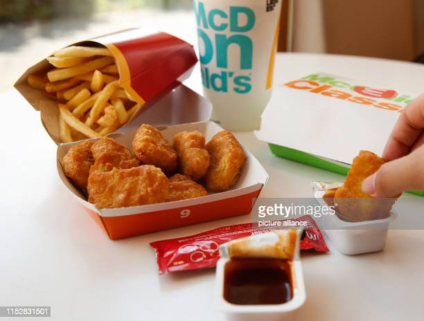 Young woman is eating Chicken McNuggets and French fries from a cardboard box, recorded at a McDonald's branch. The fast food chain McDonald's wants...