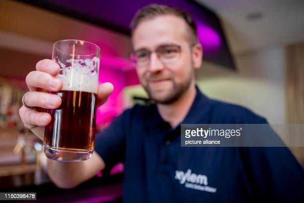 ILLUSTRATION Jens Scheideler Product Manager Water Reuse at Xylem holds a glass of beer brewed from wastewater at the IWA Water Reuse 2019 conference...
