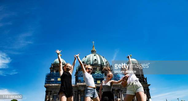 Lena Mette Josefine and Sophia from Lübeck jump into the air in front of the Berlin Cathedral Photo Wolfgang Kumm Paul Zinken Ralf/dpa