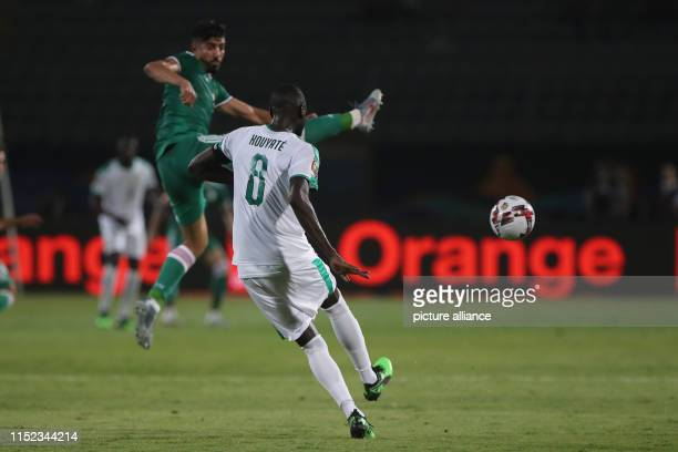 Senegal's Cheikhou Kouyate and Algeria's Ramy Bensebaini battle for the ball during the 2019 Africa Cup of Nations Group C soccer match between...