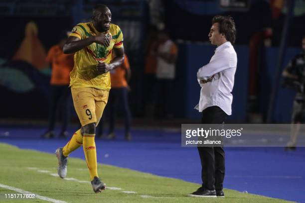 Mali's Moussa Marega celebrates scoring his side's second goal from a penalty kick while Mauritania coach Corentin Martins looks on during the 2019...