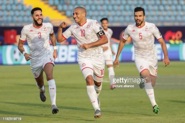 June 2019, Egypt, Suez: Tunisia's Wahbi Khazri celebrates with his teammates Dylan Bronn and Oussama Haddadi scoring his side's first goal during the...
