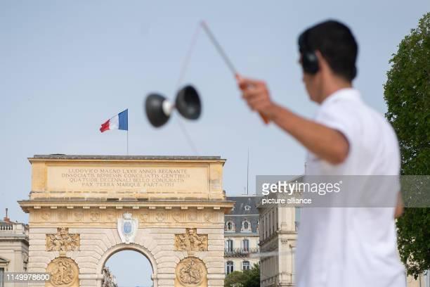 June 2019, France , Montpellier: A man plays Porte du Peyrou Diabolo in front of the Arc de Triomphe. Photo: Sebastian Gollnow/dpa