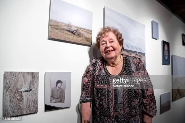 June 2019, Iceland, Reykjavik: Eva Maria Jost-Magnusson stands next to a photo of young Germans who moved to Germany in 1949 in the photo exhibition...