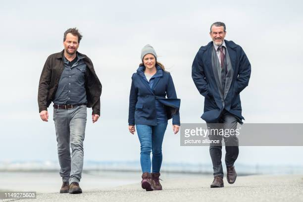 Christian Erdmann Julia Jentsch and Kai Maertens walk along the dike during the press conference to the Saturday thriller Ostfriesengrab The fourth...