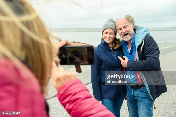 Julia Jentsch and KlausPeter Wolf are standing on the dike during the press date for the Saturday thriller Ostfriesengrab and are photographed by a...