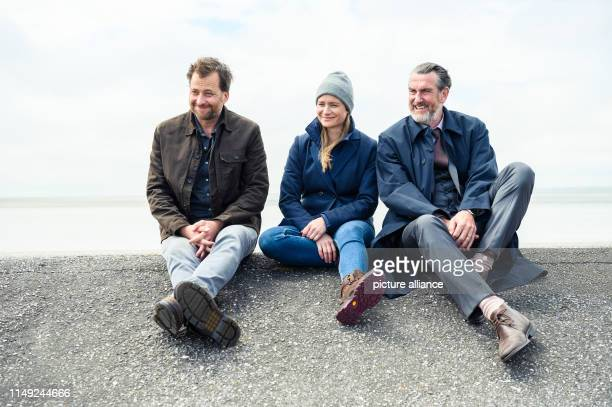 Kai Maertens Julia Jentsch and Christian Erdmann sit on the dike during the press date for the Saturday thriller Ostfriesengrab The fourth film in...